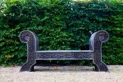 Antieke houten bank op de tuin van de kiezelsteenwerf stock foto's