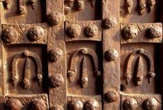 Antieke ijzerdeur die met hoeven wordt verfraaid Stock Foto