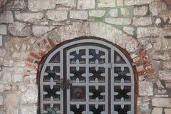 Antieke ijzerpoort in een steenmuur royalty-vrije stock afbeeldingen
