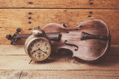 Antieke klok en oude viool over uitstekende houten lijst Stock Foto