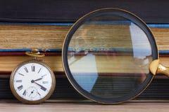 Antieke klok met loupe op boekenachtergrond Stock Foto's