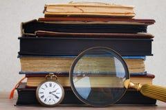 Antieke klok met loupe op boekenachtergrond Royalty-vrije Stock Afbeeldingen