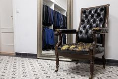 Antieke leunstoel in een de montagewinkel van de kledingsopslag stock fotografie