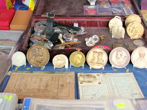Antieke muntstukken, medailles en diploma's voor verkoop in een vlooienmarkt stock afbeeldingen