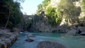 Antieke Oluk-Brug over de kreek van Kopru Irmagi in het nationale park van Koprulu Kanyon in Turkije stock video