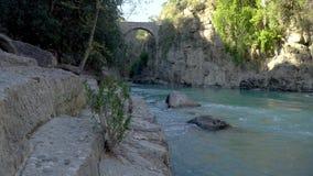 Antieke Oluk-Brug over de kreek van Kopru Irmagi in het nationale park van Koprulu Kanyon in Turkije stock footage