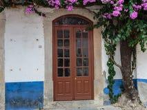 Antieke Portugese Architectuur: Oude Bruine Deur dichtbij Vegetatie in Obidos Main Street Portugal Stock Foto