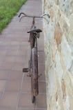 Antieke of retro geoxydeerde fiets buiten op een steenmuur Stock Fotografie