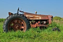 Antieke Rode die Tractor in Gras wordt geparkeerd Stock Fotografie