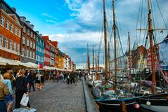 Antieke schepen in Nyhavn, Kopenhagen, DK terwijl de toeristen het district bewonderen stock foto