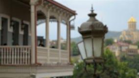 Antieke straatlantaarn dichtbij de oude bouw met open terras, regenachtige dag in Tbilisi stock videobeelden