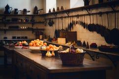 Antieke XIX een eeuw oude keuken met hulpmiddelen, pannen, potten en voedselingrediënten stock foto
