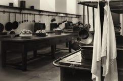 Antieke XIX een eeuw oude keuken met hulpmiddelen, pannen, potten en voedselingrediënten stock afbeelding