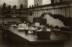 Antieke XIX een eeuw oude keuken met hulpmiddelen, pannen, potten en voedselingrediënten royalty-vrije stock afbeeldingen