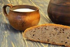 Antieke zeldzame kleikop met melk, zachte heerlijke aromatische eigengemaakte roggebrood en kleikruik op de achtergrond op ruwe n royalty-vrije stock afbeeldingen