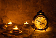 Antient clock 2. Antient alarm clock with three candles royalty free stock images