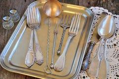 Antigüedades - cubiertos, cucharas, bifurcaciones, cuchillos en una bandeja Fotografía de archivo libre de regalías