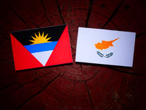 Antigua and Barbuda flag with Cypriot flag on a tree stump isola Royalty Free Stock Photo