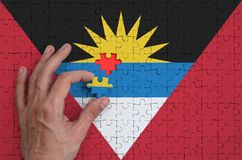 Antigua and Barbuda flag is depicted on a puzzle, which the man`s hand completes to fold.  royalty free illustration