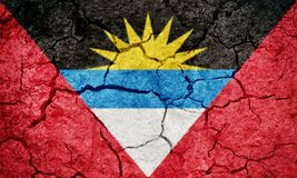 Antigua and Barbuda flag. On dry earth ground texture background stock images