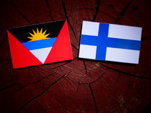 Antigua and Barbuda flag with Finnish flag on a tree stump isola Royalty Free Stock Photos