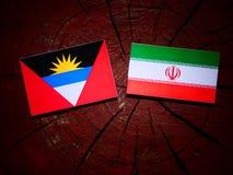 Antigua and Barbuda flag with Iranian flag on a tree stump isola Stock Photo