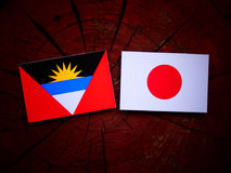 Antigua and Barbuda  flag with Japanese flag on a tree stump isolated Royalty Free Stock Image