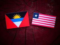 Antigua and Barbuda flag with Liberian flag on a tree stump isol Royalty Free Stock Image