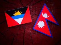 Antigua and Barbuda flag with Nepali flag on a tree stump isolat Royalty Free Stock Photos