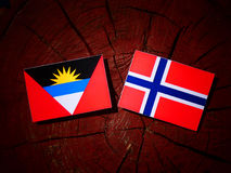 Antigua and Barbuda flag with Norwegian flag on a tree stump iso. Lated Stock Photo