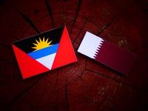 Antigua and Barbuda  flag with Qatari flag on a tree stump isolated Stock Photos