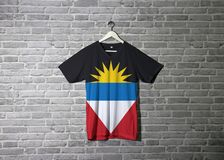 Antigua and Barbuda flag on shirt and hanging on the wall with brick pattern wallpaper. Horizontal of black blue and white with two red triangles and yellow stock photo