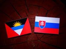 Antigua and Barbuda flag with Slovakian flag on a tree stump iso. Lated Royalty Free Stock Photo