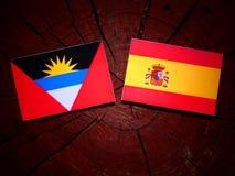 Antigua and Barbuda flag with Spanish flag on a tree stump isola Royalty Free Stock Photo