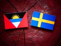 Antigua and Barbuda flag with Swedish flag on a tree stump isola Stock Image