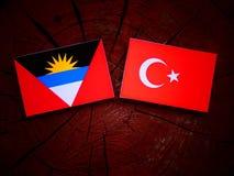 Antigua and Barbuda  flag with Turkish flag on a tree stump  Royalty Free Stock Photo