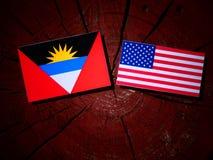 Antigua and Barbuda flag with USA flag on a tree stump  Stock Photo