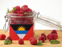 Antigua and Barbuda flag on a wooden panel with raspberries isol Stock Photos