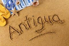 Antigua beach sand word writing. The word Antigua written on a sandy beach, with scuba mask, beach towel, starfish and flip flops Royalty Free Stock Photos