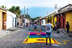 Locals working on Alfombre flower carpets on the cobbled streets of Antigua, Guatemala stock image