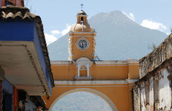 Antigua - Guatemala. An arch with a clock in the city of Antigua Guatemala with a volcano at the back Stock Image