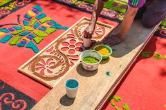 Decorating dyed sawdust Holy Thursday carpet, Antigua, Guatemala. Antigua, Guatemala - April 13, 2017: Decorating dyed sawdust Holy Thursday procession carpet in stock photos