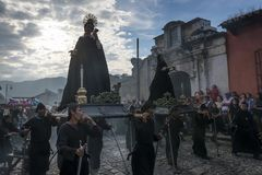 Man wearing black robes and hoods carrying floats in a street of the old city of Antigua during a procession of the Holy Week in A. Antigua, Guatemala - April 19 Stock Image