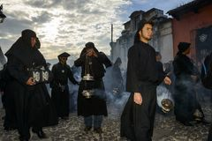 Man wearing black robes and hoods spreading incense in a street of the city of Antigua during a procession of the Holy Week in Ant. Antigua, Guatemala - April 19 Stock Image