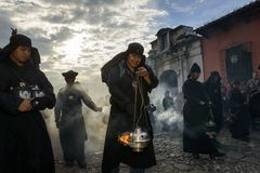 Man wearing black robes and hoods spreading incense in a street of the city of Antigua during a procession of the Holy Week in Ant. Antigua, Guatemala - April 19 Royalty Free Stock Photo