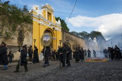 People wearing black robes and hoods during a procession of the Holy Week in Antigua. Antigua, Guatemala - April 19, 2014: People wearing black robes and hoods Royalty Free Stock Images