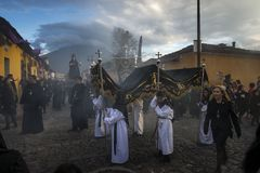 People wearing black robes and hoods in a street of the old city of Antigua during a procession of the Holy Week with a volcano in. Antigua, Guatemala - April 19 Royalty Free Stock Photography
