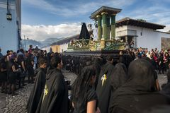 People wearing black robes and hoods in a street of the old city of Antigua during a procession of the Holy Week, in Antigua. Antigua, Guatemala - April 19, 2014 Royalty Free Stock Image
