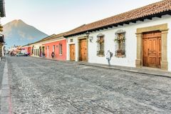 Colonial street & Agua volcano, Antigua, Guatemala. Antigua, Guatemala - March 25, 2018: Colonial street & Agua volcano at dawn on Palm Sunday in UNESCO World royalty free stock images