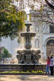 Fountain in central plaza, Antigua, Guatemala. Antigua, Guatemala - March 30, 2018: Early morning locals & tourists on Good Friday in central plaza in colonial royalty free stock photo